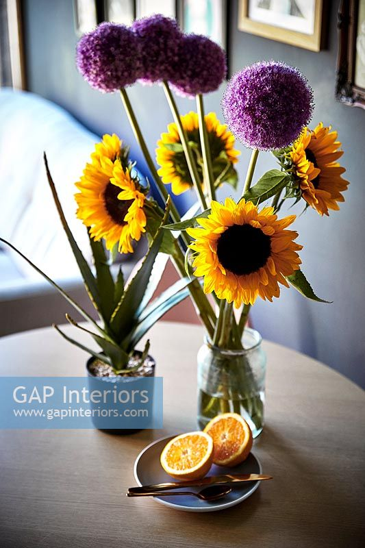 Sunflowers and alliums in vases on small dining table