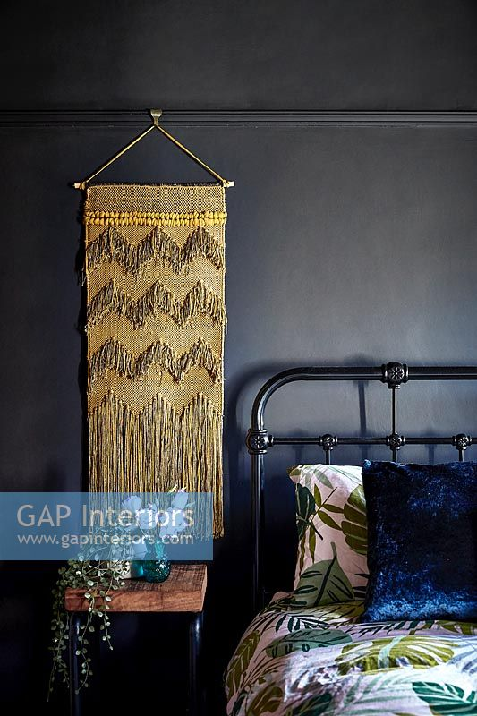 Golden wall hanging in modern bedroom with vintage iron bed frame