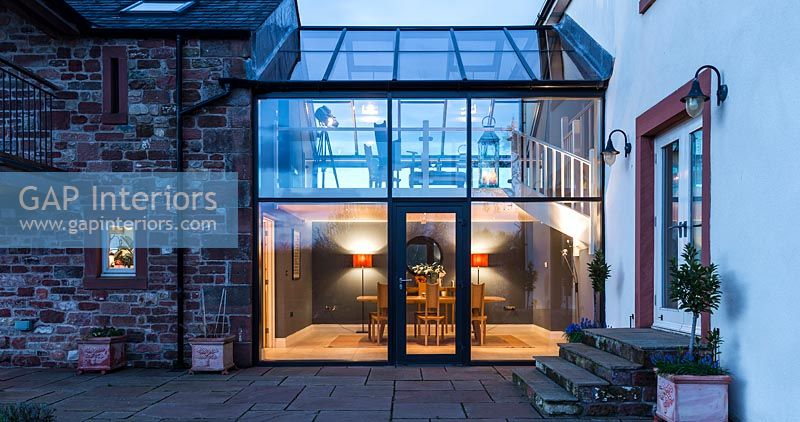 Country house exterior with modern glazed joining room illuminated in evening