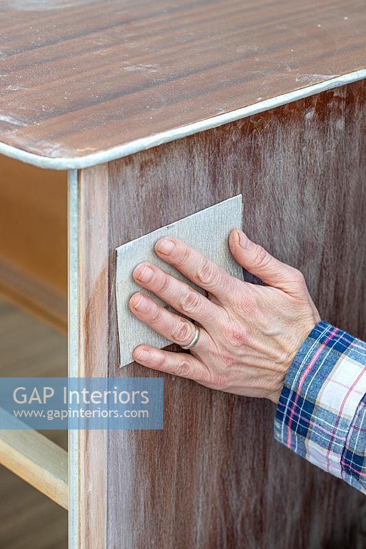 Woman using sandpaper to prepare the set of drawers for painting