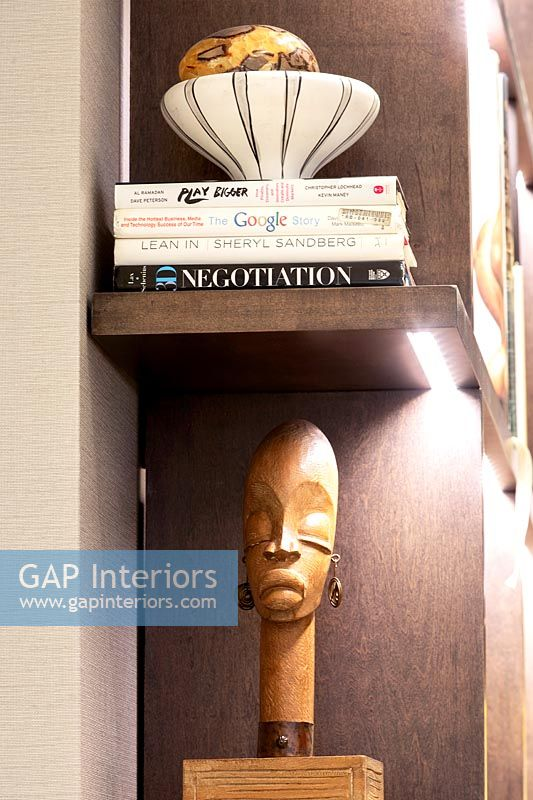 Wooden African carving on illuminated bookshelf