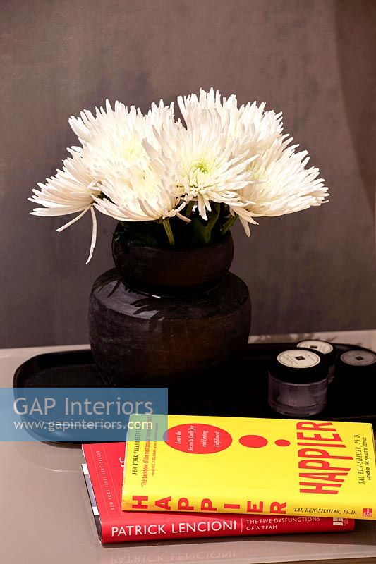 Black vase with white cut flowers on bedside table with reading material