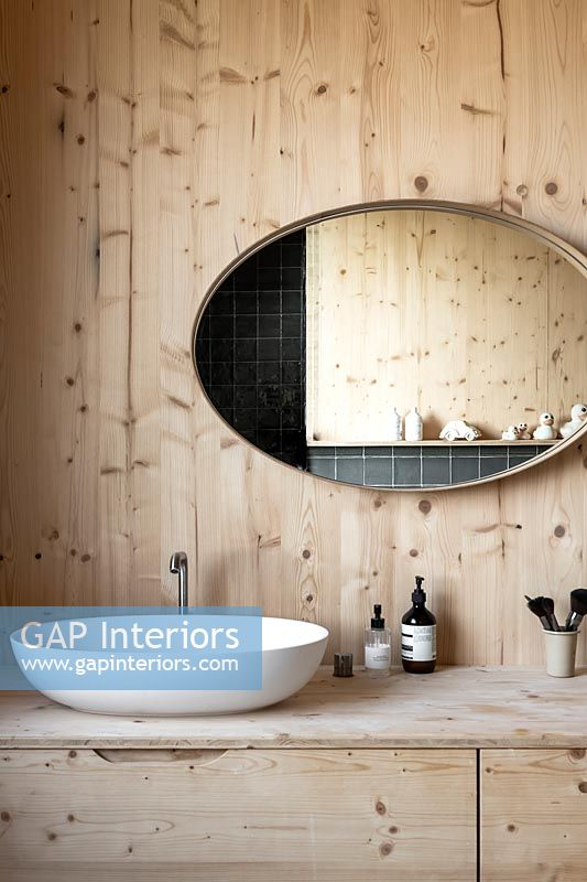 Large oval mirror above sink in wooden bathroom