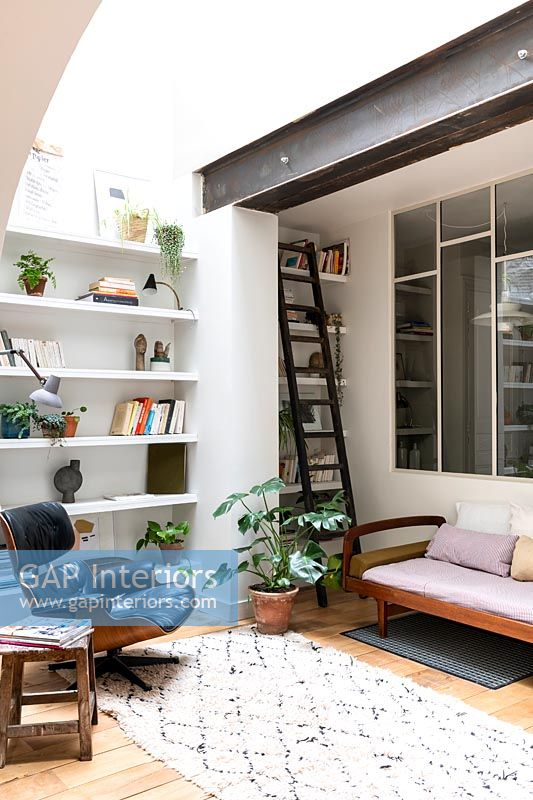 Small modern reading room with ladder next to bookshelves