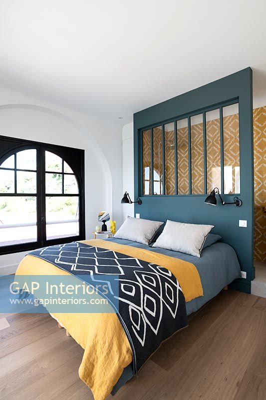 Colourful modern bedroom with headboard divider to en-suite bathroom area
