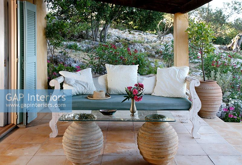 Ornate wooden sofa on covered terrace with glass and clay urn table