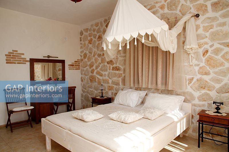 Exposed stone wall in country bedroom