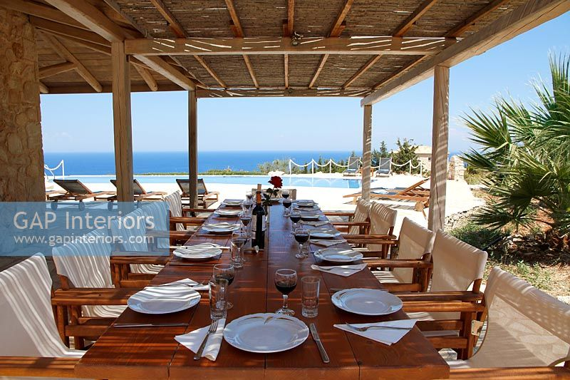Large outdoor dining area on covered terrace with view to pool and sea beyond