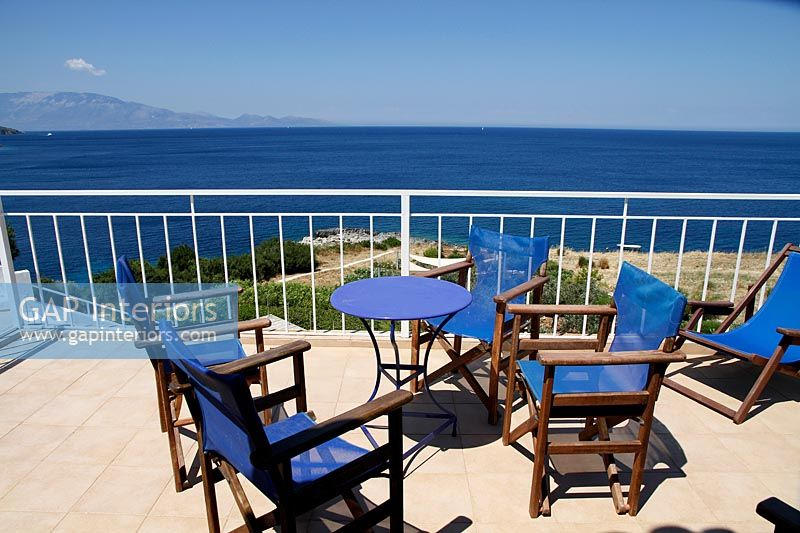 Blue furniture on terrace overlooking the sea