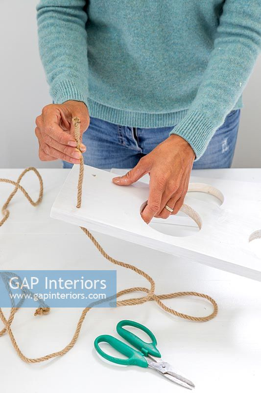 Woman threading cord or rope through the holes made in the corners of the boards