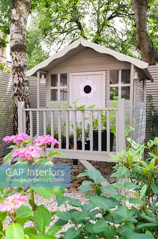 Decorative painted wooden playhouse in garden