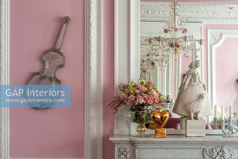 Bright pink eclectic living room with period details and ornaments