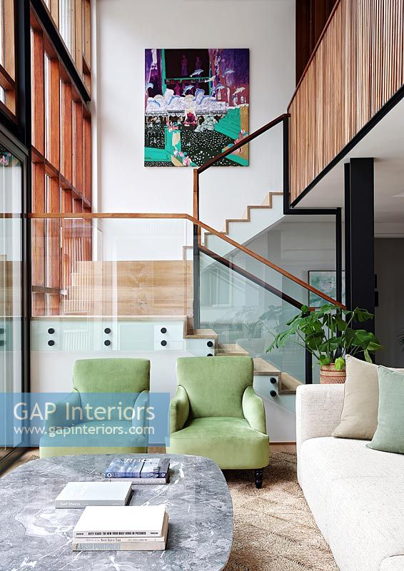 Green armchairs in modern living room with view of staircase
