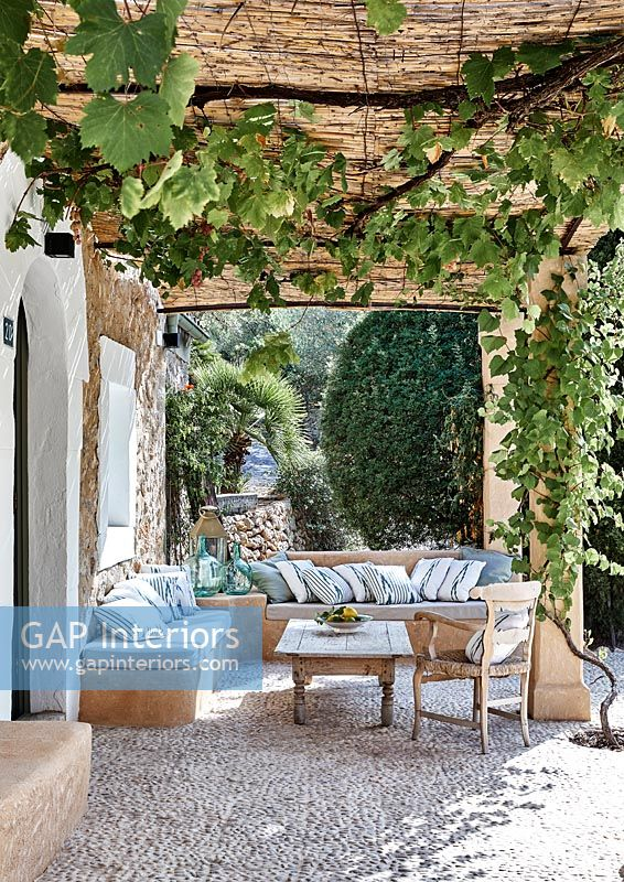 Furniture under pergola on terrace of country house in summer