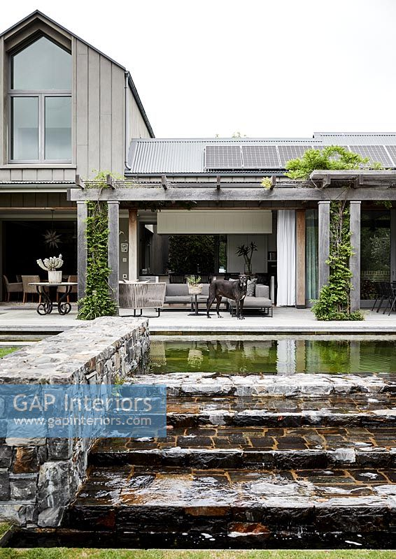 Modern country house exterior with outdoor living area on terrace