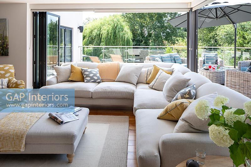 Large modular corner sofa next to open bi-fold doors in modern living room