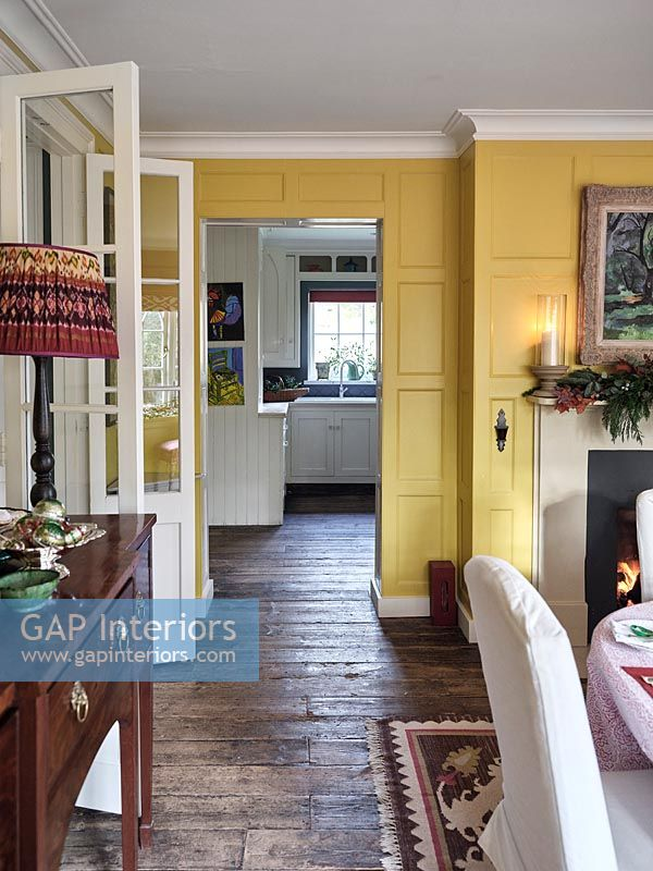 View into kitchen from yellow painted panelled dining room