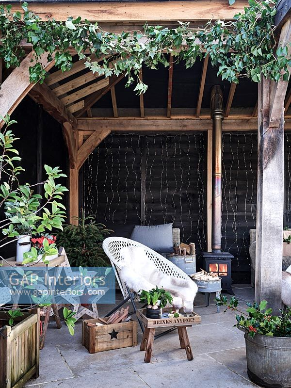Outdoor living area decorated for Christmas with lit wood burning stove