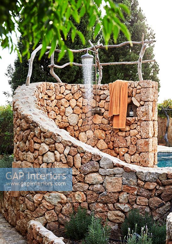 Outdoor shower set in curving stone wall
