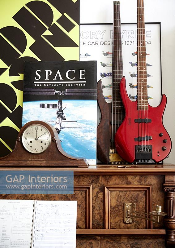Closeup of piano with guitars, antique clock and retro items
