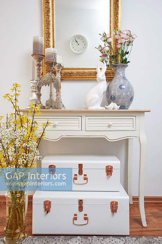 Suitcases under console table with Easter decorations and spring flowers