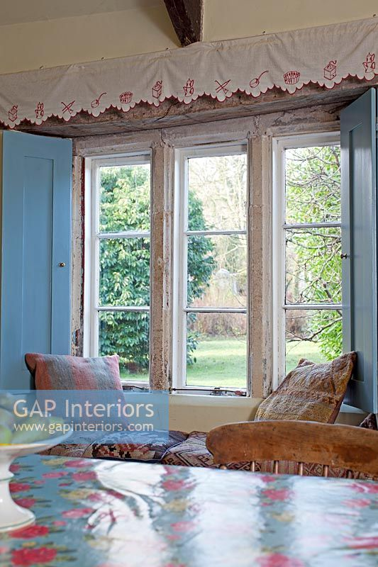 Country dining room with window seat overlooking garden