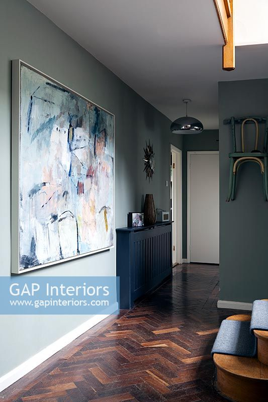Large artwork and parquet flooring in modern hallway