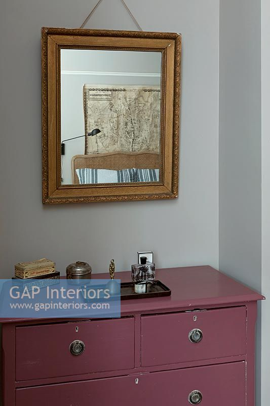 Gilded mirror over pink painted chest of drawers in bedroom