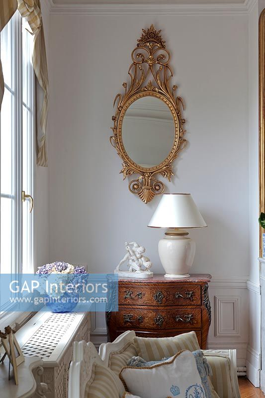 Gilded mirror and antique furniture in classic living room