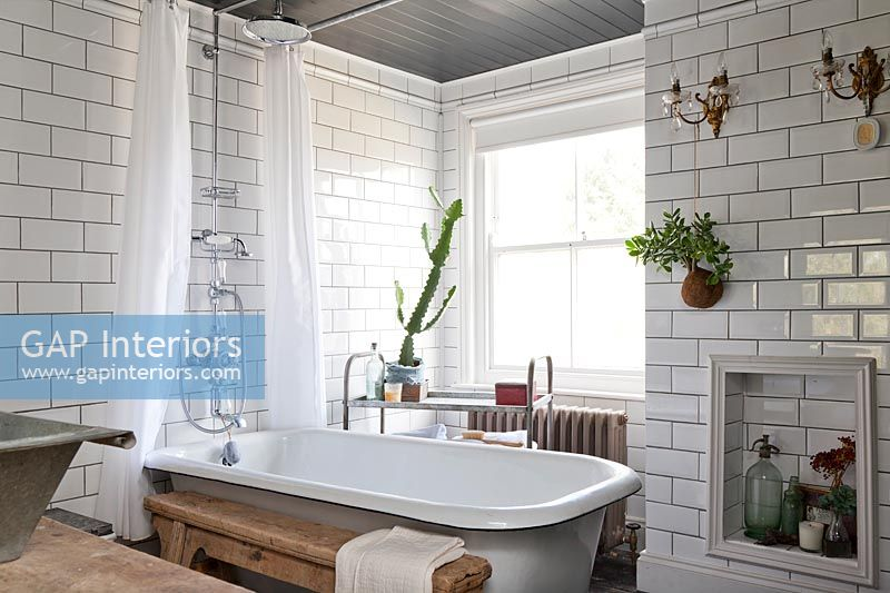 Roll top bath with white metro brick tiling