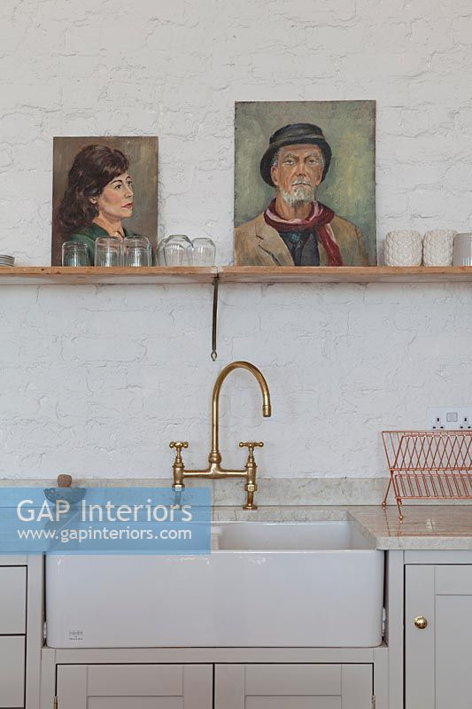 Painted portraits on shelf above butler sink