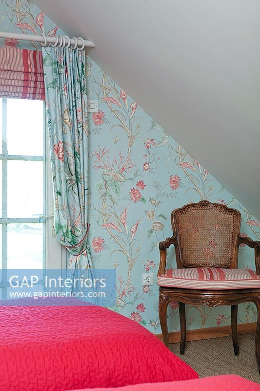 Wooden armchair against colourful floral wallpapered wall in bedroom