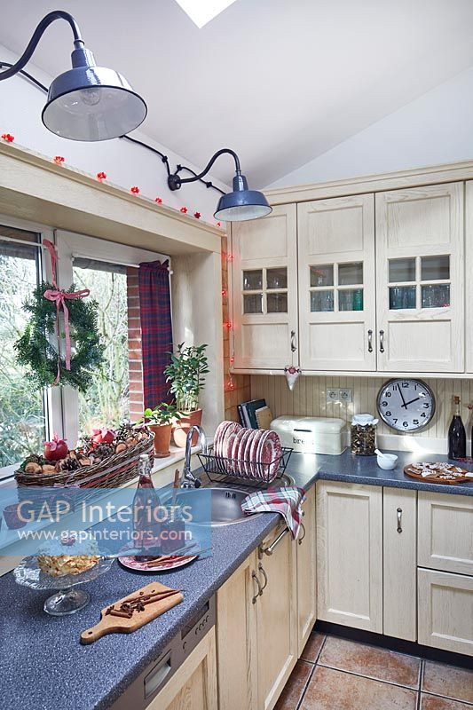Fairy lights around country kitchen window with Christmas decorations