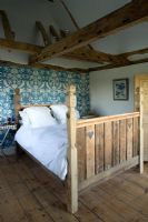 Boonshill Farm, East Sussex. Interior of bedroom with reclaimed wooden bed by mick shaw from old staircase and floorboards. peacock blue wallpaper decorates wall.