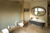Boonshill Farm, East Sussex. Interior of bathroom with roll top bath, wooden bench from india  and mirror made from old window.