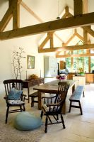 Open plan dining room and kitchen with dining table wooden beams and limestone floor