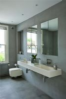 Modern bathroom with wall mounted double stone sink in grey slate tiled bathroom  twin with mirrors