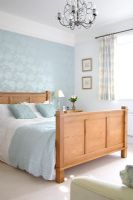 Classic bedroom with double bed and wallpapered feature wall