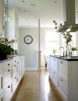 Kitchen with white units and parquet flooring