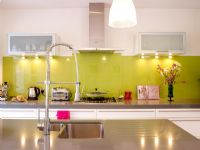 Modern kitchen with green glass splashback