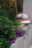 Rendered raised bed beside fireplace with Liriope muscari, candles and a large glass bowl with gerberas in garden at night