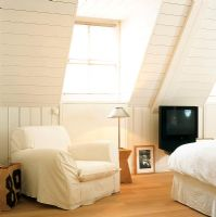 Attic bedroom with white armchair