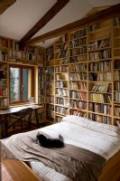 Bedroom lined with bookshelves