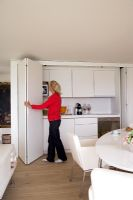 Woman opening concealed kitchen