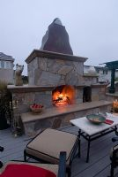 Outdoor kitchen and fireplace with fire