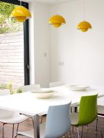 Dining area with colourful chairs and yellow pendant lights