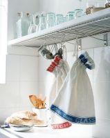 Glasses on shelf with bags made from tea towels hanging on hook