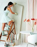 Woman hanging wallpaper on wall
