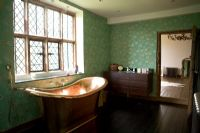 Copper bath next to lead paned window in traditional bathroom