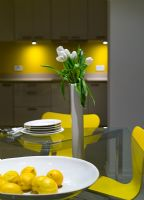 Glass dining table and yellow Jacobsen Series 7 chairs at night